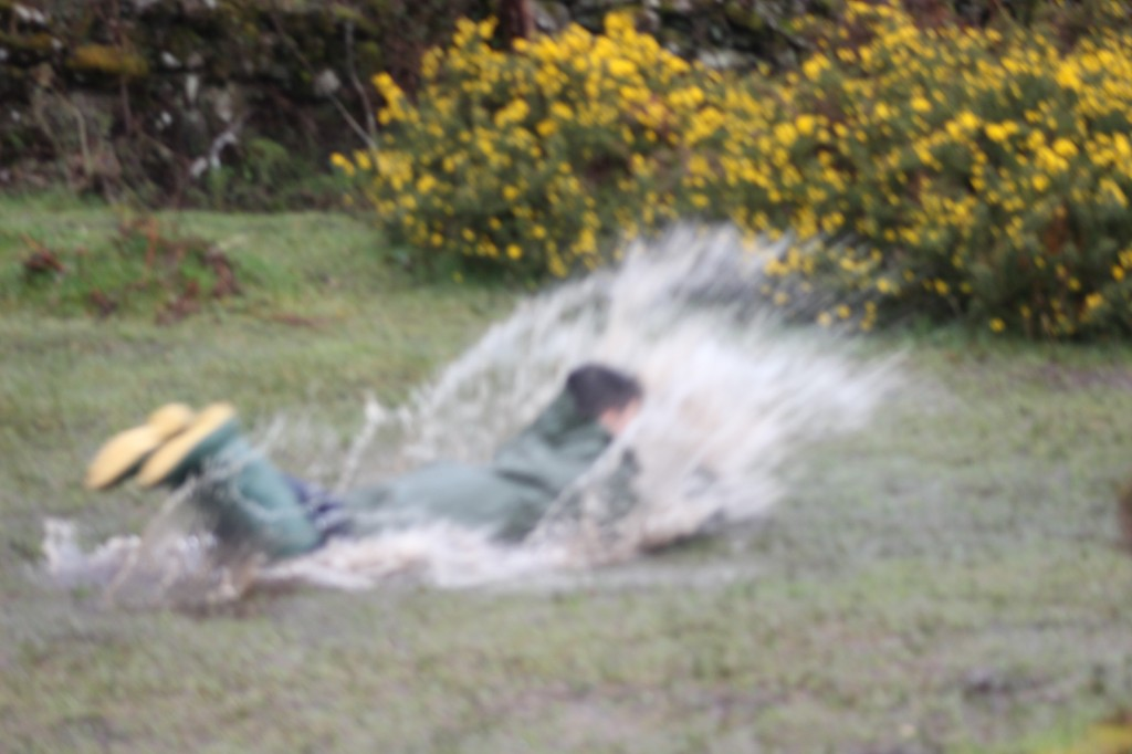 Boy sliding aling the wet grass creating a shower of water